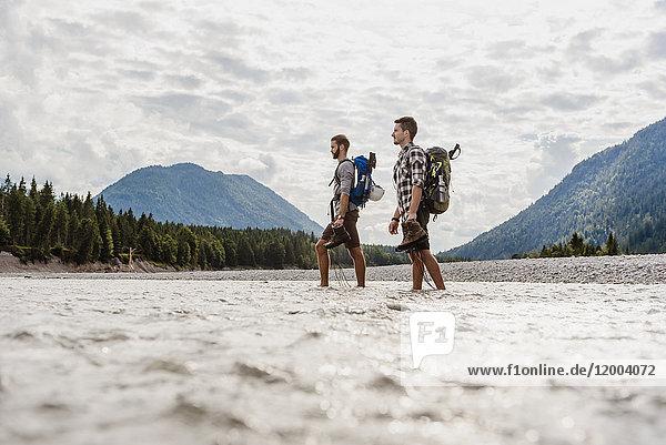 Deutschland  Bayern  zwei Wanderer mit Rucksäcken über die Isar