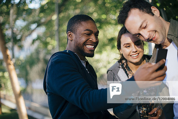 Fröhlicher Mann zeigt Freunden sein Handy