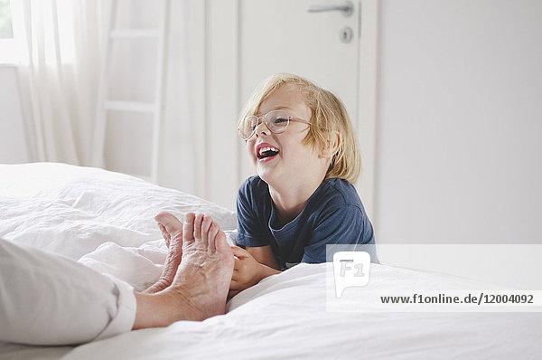 Glücklicher Enkel kitzelt Großmutters nackte Füße auf dem Bett zu Hause.