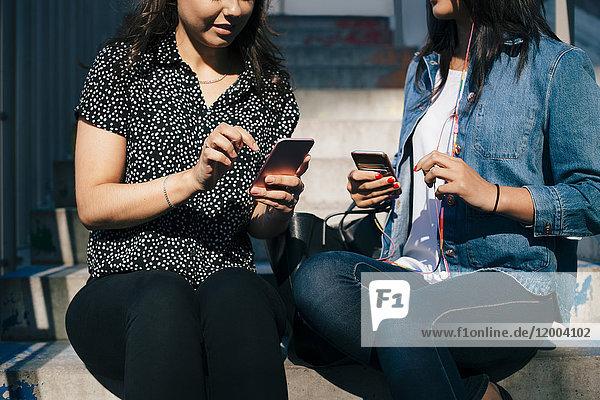 Mittelteil der weiblichen Freunde  die Smartphones benutzen  während sie auf Stufen sitzen.
