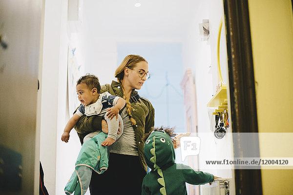 Niederwinkelansicht der Mutter mit Kindern,  die zu Hause an der Tür stehen