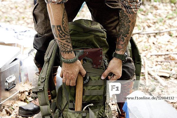 Mann mit Axt und Rucksack im Wald