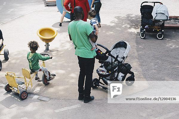 Hochwinkelansicht des Vaters, der das Kleinkind trägt, während er auf dem Dreirad im Park steht.