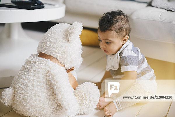 Kleinkind schaut auf den Teddybär, während es zu Hause auf dem Boden sitzt.