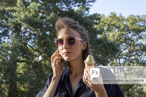 Junge Frau mit Eiszapfen mit Smartphone