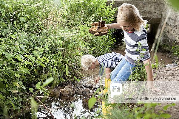 Junge und Mädchen spielen mit geschnitztem Holzboot im Bach