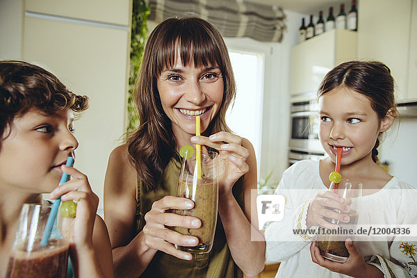 Mother and children enjoying their homemade smoothies