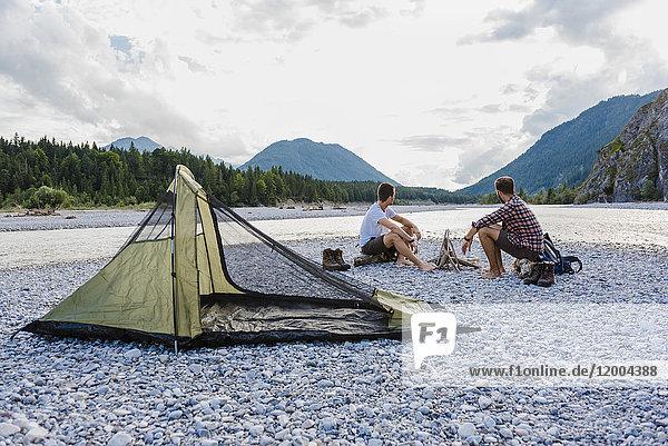 Deutschland  Bayern  zwei Wanderer  die auf Kiesbänken campen und die Aussicht genießen.