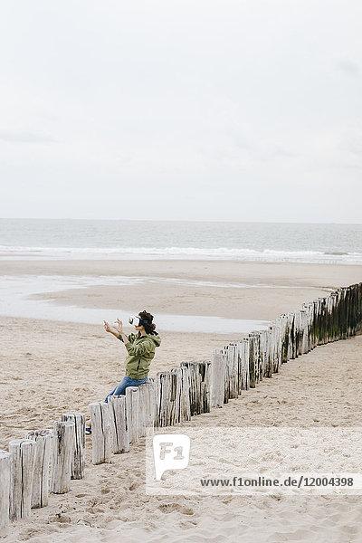 Frau auf Holzpfahl am Strand sitzend mit VR-Brille