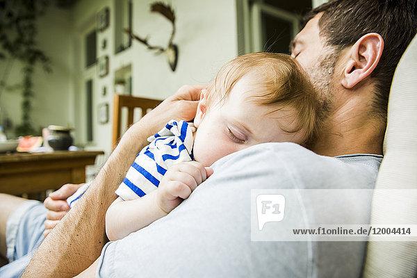 Junge schläft mit Kopf auf der Schulter seines Vaters.