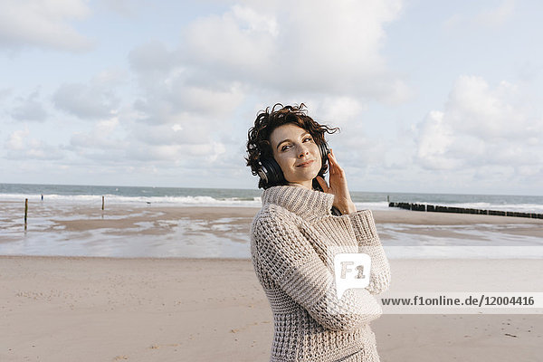Lächelnde Frau am Strand mit Kopfhörer