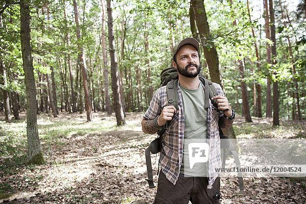 Ernsthafter Mann mit Rucksack auf einer Wanderung im Wald