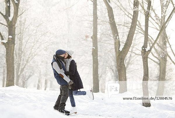 Seniorenpaar beim Umarmen und Küssen auf dem zugefrorenen See