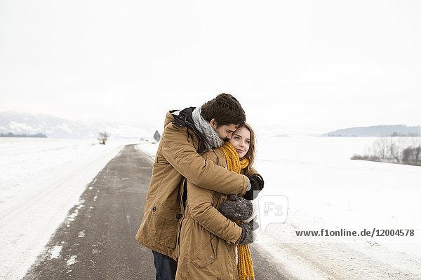 Verliebtes junges Paar steht auf der Landstraße in verschneiter Landschaft