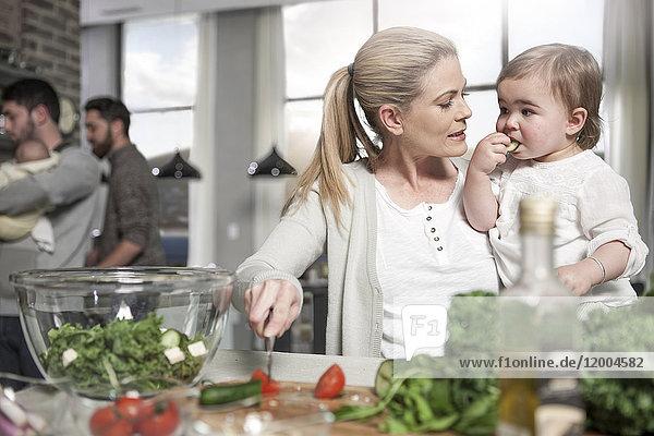Mutter hält Baby bei der Zubereitung einer gesunden Mahlzeit in der Küche.