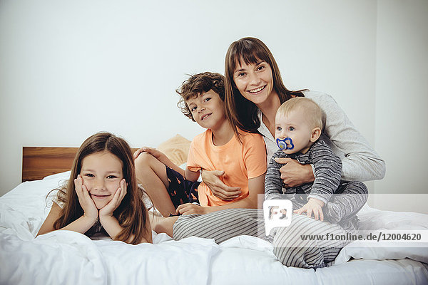 Happy mother in bed with her three children