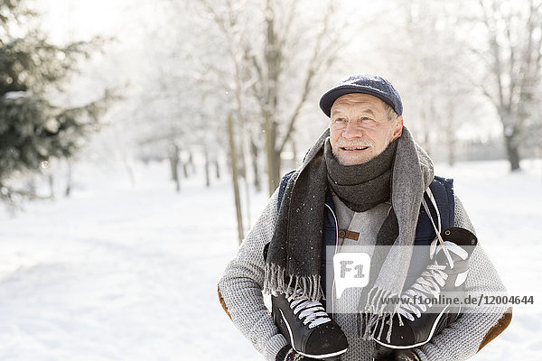 Smiling senior man with ice skates in winter forest