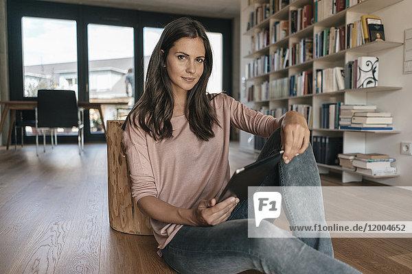 Porträt einer Frau  die sich zu Hause entspannt und eine Tablette hält.