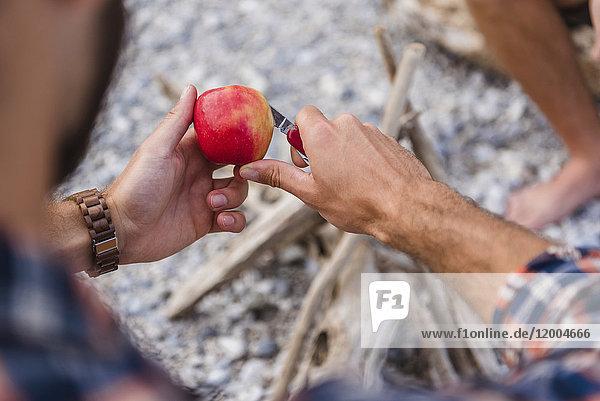Männerhand beim Apfelschneiden am Lagerfeuer