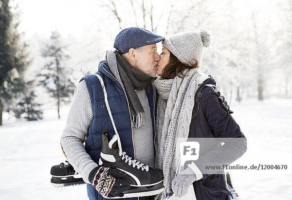 Seniorenpaar mit Schlittschuhen beim Küssen in der Winterlandschaft