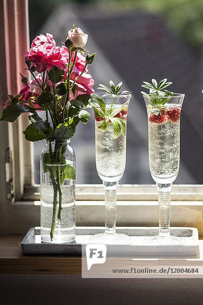 Zwei Champagnergläser Maiswein mit Himbeeren auf der Fensterbank
