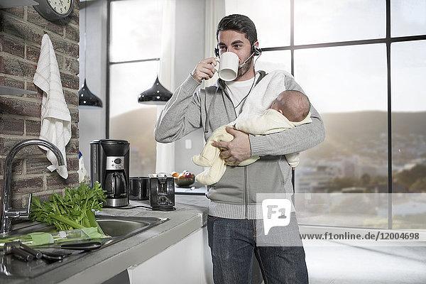 Vater mit Kopfhörer trinkt Kaffee in der Küche hält Baby