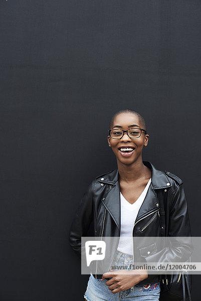 Porträt einer lachenden jungen Frau in schwarzer Lederjacke Porträt einer lachenden jungen Frau in schwarzer Lederjacke
