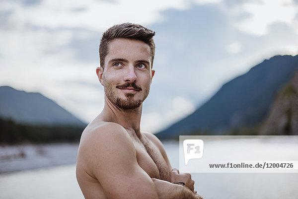 Deutschland  Bayern  Portrait eines jungen Mannes ohne Hemd in der Natur