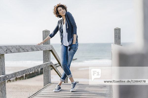 Porträt einer lächelnden Frau auf der Strandpromenade stehend