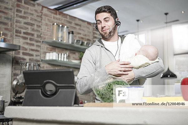 Vater mit Kopfhörer und Tablette in der Küche hält Baby