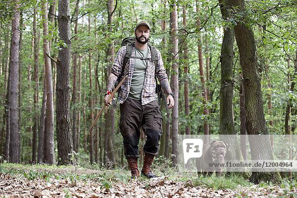 Mann mit Pfeil und Bogen spazieren mit Hund im Wald