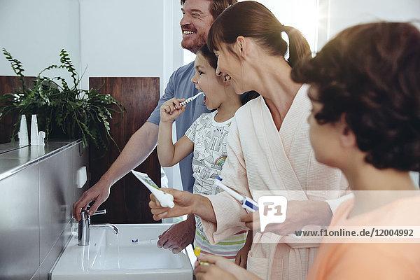 Vierköpfige Familie beim Zähneputzen im Bad