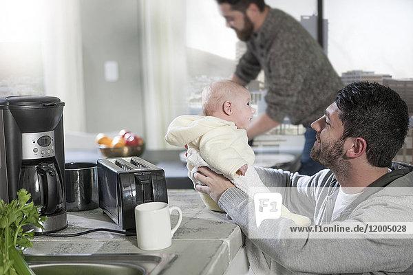 Zwei Männer mit Baby in der Küche