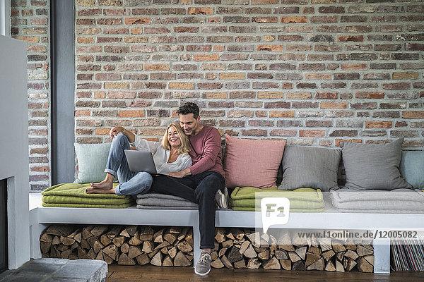 Ein Paar sitzt auf der Couch und surft im Internet.