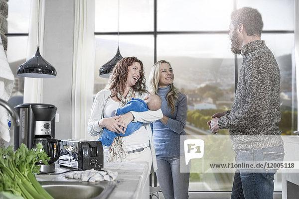 Mutter hält Baby mit Freunden zu Hause beim Kochen Besuch