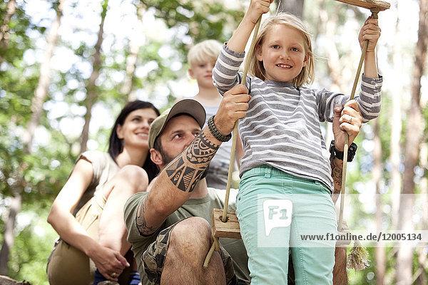 Glückliche Familie im Wald mit Mädchen auf Schaukel