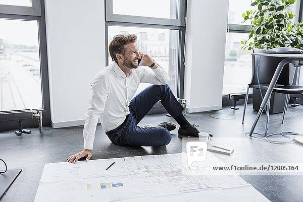 Geschäftsmann am Telefon  der auf dem Boden seines Büros sitzt.