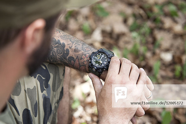 Close-up of man in forest checking the time