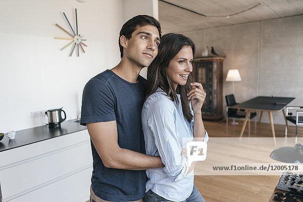 Glückliches Paar  das sich zu Hause in der Küche umarmt.