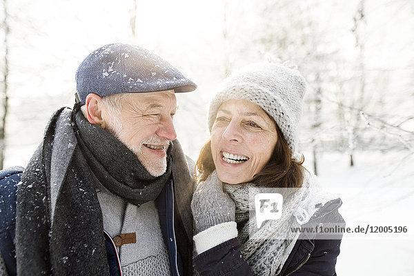 Porträt eines glücklichen Seniorenpaares in der Winterlandschaft