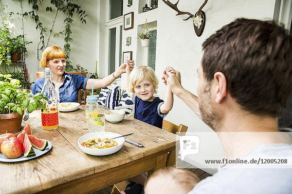 Familie zur Mittagszeit gemeinsam auf dem Balkon