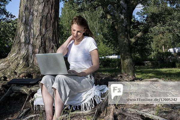Junge Frau mit Laptop im Wald