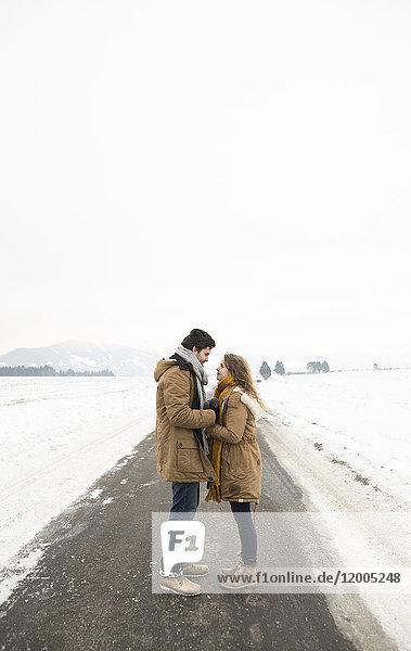 Verliebtes junges Paar steht auf leerer Landstraße in verschneiter Landschaft