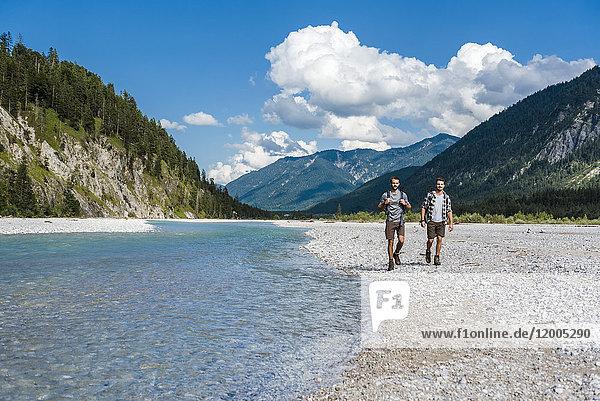 Deutschland  Bayern  zwei Wanderer am Flussufer