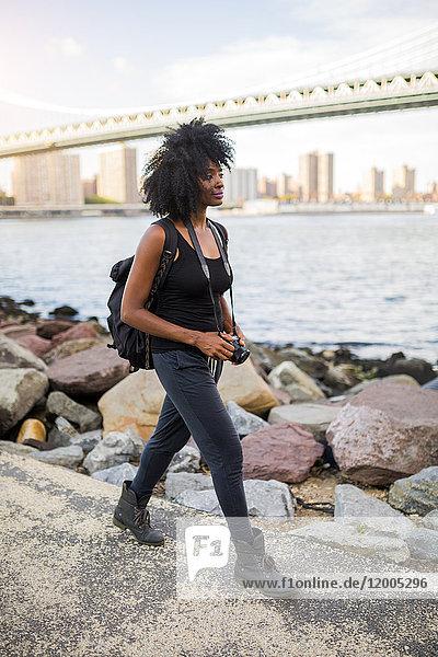 USA  New York City  Brooklyn  woman with camera walking at the waterfront