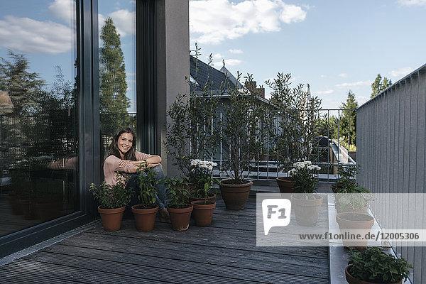 Lächelnde Frau entspannt auf dem Balkon  umgeben von Pflanzen