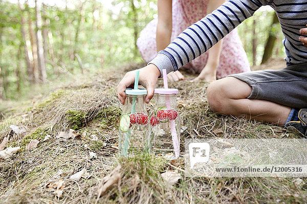 Junge greift nach einem Glas Wasser mit Gurkenscheiben und Himbeeren im Wald.