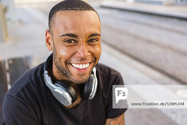 Porträt eines lachenden jungen Mannes mit Kopfhörern an der Straßenbahnhaltestelle