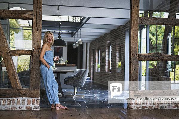 Frau steht in ihrem gemütlichen Landhaus  lächelnd