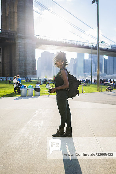 USA  New York City  Brooklyn  Frau mit Kamera stehend an der Brooklyn Bridge